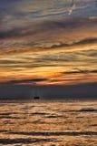 Velero en la puesta del sol en la distancia Foto de archivo libre de regalías