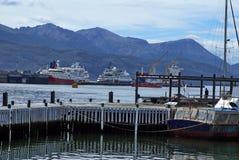 Velero en un embarcadero de madera en el puerto de Ushuaia con el embarcadero comercial en el fondo imagen de archivo