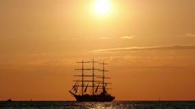 Velero hermoso de la silueta en el mar flotadores tres-masted de la nave en los altos mares en la puesta del sol almacen de metraje de vídeo