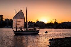 Velero que entra en el puerto cerca de Granville Island, Vancouver, con el ajuste del sol en el fondo imagen de archivo libre de regalías