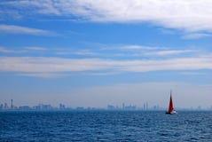 Velero rojo en el océano con el océano azul Imagenes de archivo
