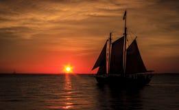 Velero silueteado contra puesta del sol Fotografía de archivo