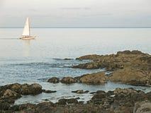 Velero y costa rocosa Ogunquit Maine Foto de archivo