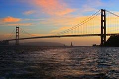 Velero y puente Golden Gate en la puesta del sol con las nubes Fotografía de archivo
