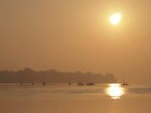 Veleros en el agua en la puesta del sol Imagen de archivo