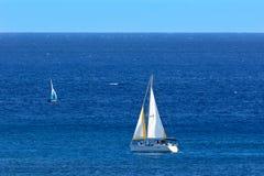 Veleros en el océano azul profundo con horizonte claro del cielo Fotos de archivo libres de regalías