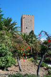 Velez Malaga Castle Tower. View of the Arabic castle tower (Torre del Homenaje) with palm trees in the foreground, Velez Malaga, Costa del Sol, Malaga Province Royalty Free Stock Photography