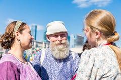 Velho e novo Um homem idoso de sorriso com uma barba cinzenta em um traje nacional está com duas jovens mulheres foto de stock