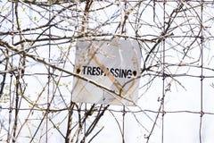 Velho e resistido nenhum sinal infrinjindo afixou à cerca de fio, segura Fotografia de Stock Royalty Free