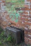 Velho, marrom, coberto com a mala de viagem da Web perto de uma parede de tijolo suja assim foto de stock royalty free