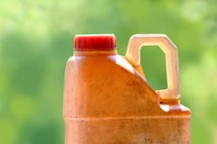 Velhos amarelos do galão plástico do lubrificante do óleo no fundo verde borrado, fecham-se acima do galão velho e sujo do óleo d imagem de stock