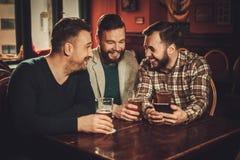 Velhos amigos alegres que têm o divertimento e que bebem a cerveja de esboço no bar fotografia de stock