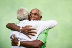 Velhos amigos, dois homens americanos africanos superiores que encontram-se e que abraçam