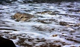 Sea water foaming between rocks. Veliki Zal beach at Dubravice near Dubrovnik, Croatia Stock Photos
