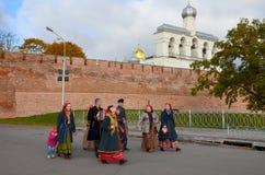 Velikiy Novgorod, Rusland - Oktober 4, 2014: Mannen en vrouwen, de de gekleed in traditionele kostuums, lopen langs de weg van he stock afbeeldingen