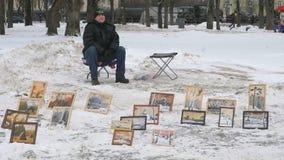 The artist selling drawn on canvas paintings. VELIKIY NOVGOROD, RUSSIA - FEBRUARY 23, 2017: Artist sitting on chair selling paintings drawn watercolour on canvas stock video footage