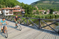 VELIKO TARNOVO, БОЛГАРИЯ - 30-ОЕ ИЮЛЯ 2015: 2 молодых мальчика пересекая деревянный мост велосипедом на реке Yantra Стоковая Фотография