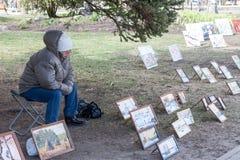 VELIKY诺夫哥罗德,俄罗斯- 5月13日:妇女卖图片在克里姆林宫墙壁,俄罗斯- 2017年5月13日 免版税库存图片