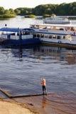 Veliky Novgorod, Rosja, Maj 2018 Chłopiec połów w wiośnie na Volkhov rzece blisko mola motorowi statki obraz stock