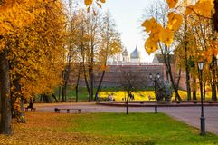 Kremlin park and St Sophia cathedral with walking tourists in sunny October evening in Veliky Novgorod park, Russia royalty free stock photo