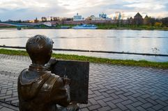 Sculpture of the drawing boy at the embankment of the Volkhov river in Veliky Novgorod, Russia, autumn view. VELIKY NOVGOROD, RUSSIA -OCTOBER 19, 2017. Sculpture Stock Photography