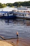 Veliky Novgorod, Ryssland, Maj 2018 En pojke som på våren fiskar på den Volkhov floden nära pir av motorskepp fotografering för bildbyråer