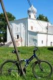 Veliky Novgorod, Ryssland, Maj 2018 Forntida rysk ortodox kyrka och modern cykel som en kontrast royaltyfri foto