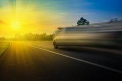 Velocidad muy rápida del coche en el camino por la tarde y la puesta del sol de los haces Usando concepto automotriz del fondo de Foto de archivo libre de regalías
