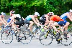 A velocidade do passeio de Triathletes dá um ciclo para a frente e para trás durante a competição do triathlon Foto de Stock