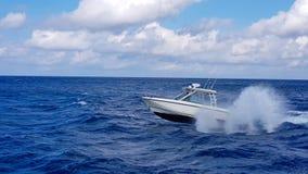 Velocidade que pesca o barco macio que salta as ondas no mar e que cruza o dia azul do oceano no Bahamas Água bonita azul foto de stock