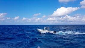Velocidade que pesca o barco macio que salta as ondas no mar e que cruza o dia azul do oceano no Bahamas Água bonita azul fotos de stock