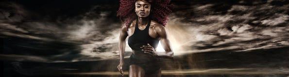 Velocista atlético forte da mulher, correndo no fundo escuro que veste no sportswear Motivação da aptidão e do esporte corredor foto de stock