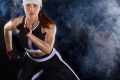 Velocista atlético forte da mulher, correndo no fundo preto que veste no sportswear Motivação da aptidão e do esporte fotos de stock royalty free