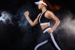 Velocista atlético forte da mulher, correndo no fundo preto que veste no sportswear Motivação da aptidão e do esporte funcionamen fotos de stock