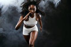 Velocista preto atlético forte da mulher da pele, correndo no fundo com o fumo que veste no sportswear Aptidão e esporte fotos de stock royalty free