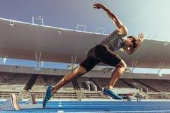 Velocista que descola do bloco começar na pista de atletismo imagem de stock royalty free