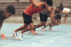 Velocistas que decolam para uma raça na pista de atletismo fotos de stock