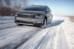 Velocità moderna grigia dell'azionamento dell'automobile sulla strada al giorno di inverno Fotografia Stock