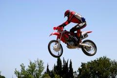 Velomotor de Moto X que salta através do ar em um dia ensolarado quente com o céu azul grande Fotos de Stock