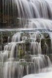 Velos del agua que bajan en pasos de progresión de la roca con el musgo Foto de archivo libre de regalías