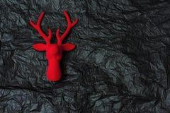 Veludo vermelho da rena decorativa do Natal no backgrou de papel preto Fotos de Stock