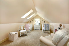 Velux nursery room. Ivory vaulted ceiling nursery room with two cribs, rocking chair and armchair. Room has two velux windows stock image