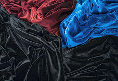 Velvet. Blue red and black glossy velvet is formative folds and light-shadow picture Royalty Free Stock Image