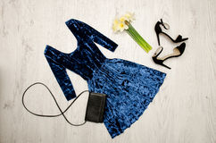 Velvet blue dress, black shoes, clutch and a bouquet of daffodils. Fashionable concept. Wooden background Stock Images