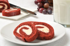 Velvet cake roll. Sliced red velvet cake roll with a glass of milk Stock Photography