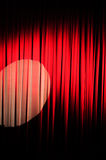The Velvet Curtain Series. Red velvet stage curtain with a spotlight on it.  Vignetting added for effect Royalty Free Stock Images