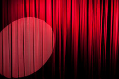 The Velvet Curtain Series. Red velvet stage curtain with a spotlight on it.  Vignetting added for effect Stock Image