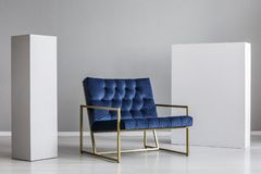 Velvet petrol blue armchair between two white blocks of wood.  stock photos