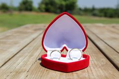 A velvet red box with a pair of gold wedding rings Stock Photo