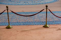 Velvet rope and metal stand near blue carpet stock photography